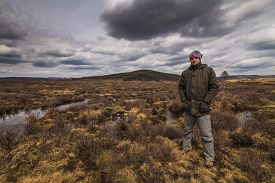 picture of marshlands  - Man traveler on marshland against the backdrop of rain clouds - JPG