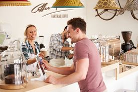 stock photo of cafe  - Young men paying for order in a cafe - JPG
