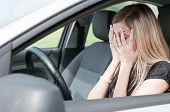 stock photo of shy woman  - Young woman with hands on eyes sitting depressed in car - JPG