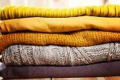 Beautiful Photo Of A Pile Of Knitted Yellow Woman Sweaters. Woman Fashion. Autumn Clothing. poster