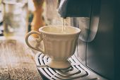 Coffee machine making fresh coffee with visible steam over cup. poster
