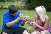 Boy And Girl Feeding Fawn