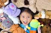 stock photo of mating bears  - A young girls in the middle of alot of stuffed animals - JPG