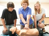 Teacher demonstrates CPR life saving techniques for her teenage students.