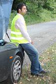 Man sat by broken-down car