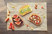 Delicious toasts with jam and chocolate paste on parchment poster