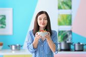 Young woman holding bowl of tasty oatmeal porridge in kitchen poster