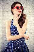 Portrait of beautiful girl with sunglasses in a blue dress with white dots. Pin-up style. poster