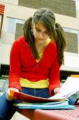 stock photo of bagpack  - young student study her notes sit on a red bench - JPG