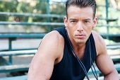 stock photo of bleachers  - Portrait of a young athletic man with jump rope sitting in the bleachers - JPG