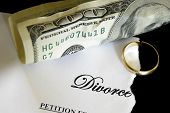 stock photo of divorce-papers  - torn divorce decree and cash with broken wedding ring - JPG