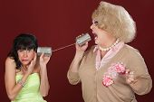 image of cross-dresser  - Woman with friend in drag talk through tin cans - JPG