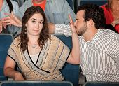 stock photo of grandstand  - Irritated girlfriend stops misbehaving boyfriend in theater - JPG