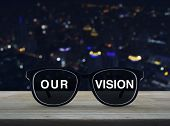 Black Glasses With Our Vision Text On Wooden Table Over Blur Colorful Night Light Office City Tower  poster