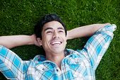 Happy Young Man Lying In The Grass