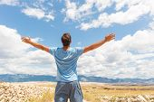 Rear View Of Casual Sporty Man Standing On A Dirt Country Road Rising Hands Up To The Clouds On A Bl poster