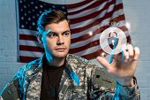Selective Focus Of Handsome Soldier Pointing With Finger At Padlock Near American Flag poster