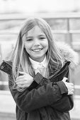 Kid Smiling Girl Wear Coat Jacket With Fur On Hood But Feels Cold. Cold Weather Concept. She Is Free poster