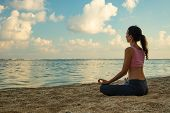 Lotus Yoga Pose. Yoga At The Beach. Young Woman Sitting On Sand, Meditating, Practicing Yoga And Pra poster