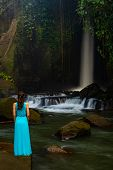 Young Traveler Woman At Waterfall In Tropical Forest. Caucasian Woman Wearing Long Blue Dress. View  poster