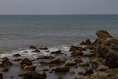 Rocky Seashore With Mist On The Water. Natural Scenery Of Dark Day. Summer Travel Background. India, poster