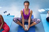 Portrait of African-american  fit woman performing yoga on a exercise mat in fitness center. Bright  poster