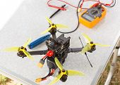 A Fpv High-speed Racing Drone Copter And Multimeter Lying On The Table poster