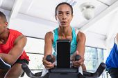 Close-up of African-american fit woman exercising on exercise bike in fitness center. Bright modern  poster