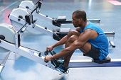 Side view of African-american Fit man exercising on rowing machine in fitness center. Bright modern  poster