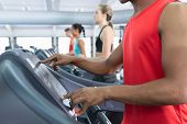 Close-up of African-american fit man operating treadmill while exercising on treadmill in fitness ce poster
