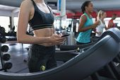 Mid section of Caucasian fit woman using mobile phone while exercising on treadmill in fitness cente poster