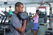 Side view of African-american Fit man exercising with dumbbells in fitness center. Bright modern gym poster