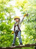 Child Boy Having Fun At Adventure Park. Carefree Childhood. Child Climbing On High Rope Park. Happy  poster
