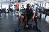Front view of African-american fit man exercising with dumbbells in fitness center. Bright modern gy poster