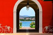 Resort Landscape. Red Arch Overlooking The Seashore And The City By The Sea. Summer Croatian Holiday poster