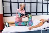 Front view of Caucasian Female trainer assisting disabled active Caucasian senior woman to stretchin poster