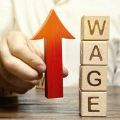 Businessmans Hand Holds Red Arrow Up Near Wooden Blocks With Word Wage. Salary Increase Concept. Wa poster