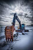 Old excavator with excavator bucket in winter. Road construction in snow. Lofoten islands, Norway. H poster