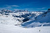 View of a ski resort piste with people skiing in Dolomites in Italy poster