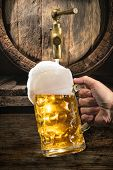 Hand of man is pouring a large lager beer in tap from wooden beer barrel. Background for Oktoberfest poster