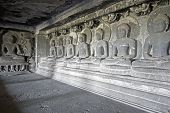 picture of ellora  - Seven images of Buddha in meditation carved out of stone inside a Buddhist rock cave  - JPG