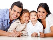 stock photo of hispanic  - Beautiful family portrait lying on the floor  - JPG