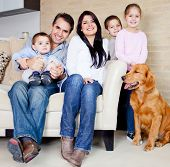 Big family at home with a dog, all looking very happy