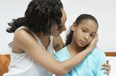 African American woman comforting sick daughter at home