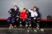 stock photo of hockey arena  - Three Youth Boys Hockey Players Pose in Dressing Room in their equipment - JPG