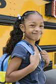 Portrait of a cute girl with backpack standing against school bus