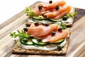 Healthy lunch of crispbread with smoked salmon, capers, cucumber, lettuce and cream cheese.