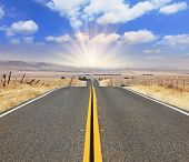 The bright sun illuminates the ideal  highway. The magnificent road through boundless to the desert