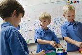 Three happy preadolescent boys solving puzzle game in a playschool