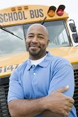 pic of bus driver  - Portrait of a confident driver with arms crossed standing against bus - JPG
